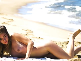 Micro body MILF Lily Chey suntanning on the top of the beach