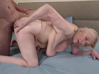 A broad in the beam hairy dude is fucking a horny old granny on the bed